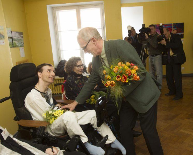 ANDEKAS KUNSTNIK: Jalaga maaliv Meelis Luks saab riigikogu esimehelt Eiki Nestorilt tänukimbu. (Arno Saar)